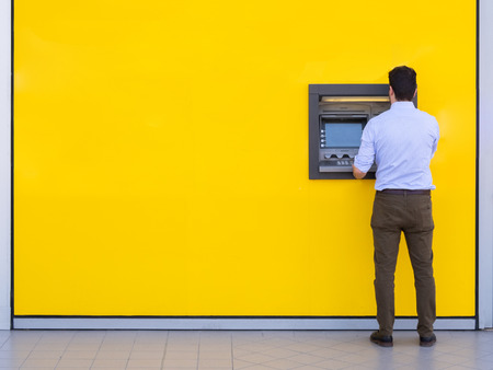 Man using a credit card in an atm for cash withdrawal Stock Photo