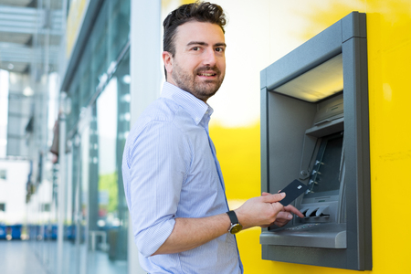 Man using a credit card in an atm for cash withdrawal
