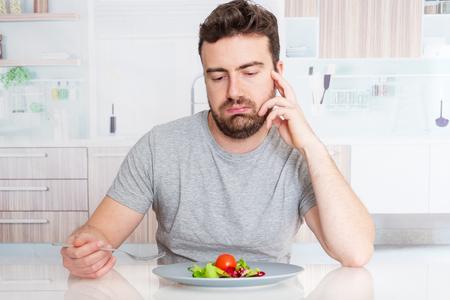 Régime d'homme triste prêt à manger de la salade pour perdre du poids