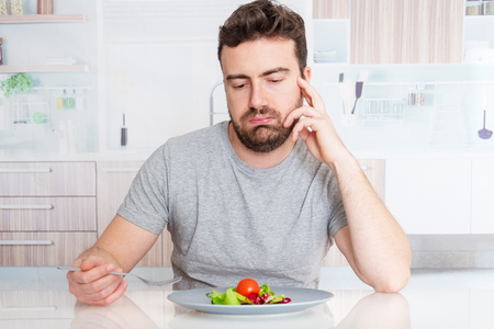 Sad man diet ready to eat salad for weight loss Фото со стока