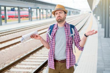 Turista triste y enojado esperando el tren.