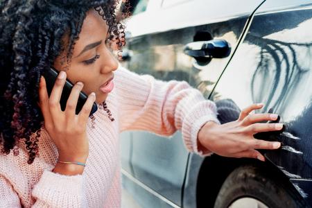 Femme noire se sentant triste après avoir gratté la carrosserie de la voiture