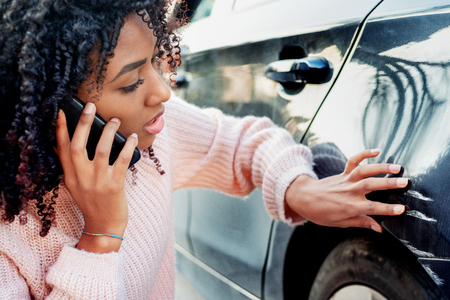 Zwarte vrouw verdrietig na krassen op carrosserie car