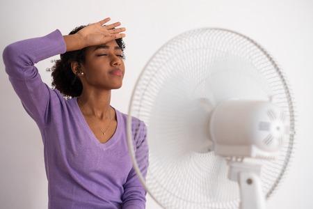 Mujer negra refrescante delante de un ventilador durante el calor del verano