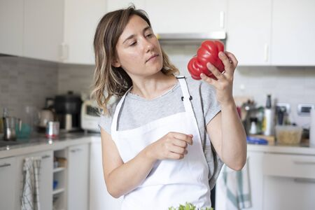 Woman portrait while cooking tomatoes in the kitchen Banque d'images