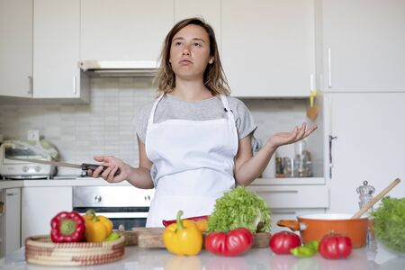 Woman stressed portrait while cooking in the kitchen Stok Fotoğraf