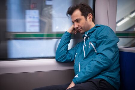 Sleepy young man feeling sad in the train in the morning