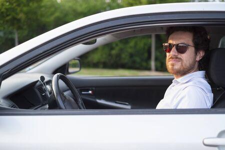 Fröhliches Mannporträt, das in seinem Auto sitzt