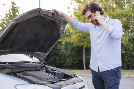 Calling roadside service after car engine breakdown Stockfoto