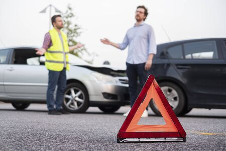 Two men reporting a car crash for the insurance claim, main focus on the red triangle Zdjęcie Seryjne