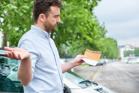 Angry man finds parking ticket after parking time limit expired Archivio Fotografico