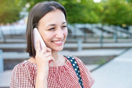Cheerful woman talking on the phone in urban city street Imagens