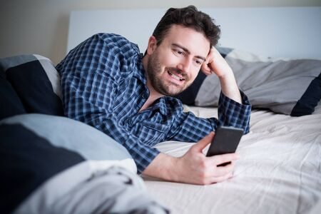 Man using mobile phone lying in his bed