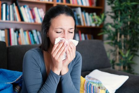 Sick woman covered by a blanket on the sofa with high fever and flu