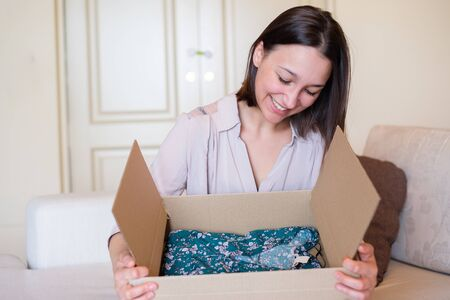 Happy woman unboxing a gift after shipping Banco de Imagens