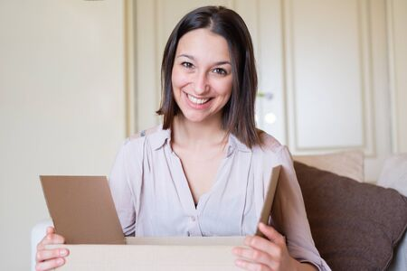 Cheerful woman portrait opening a delivered package Banco de Imagens - 132028609