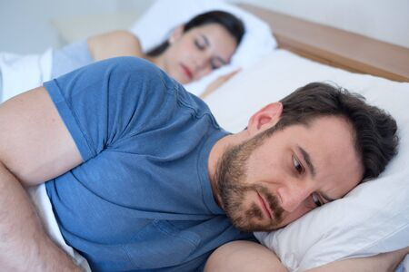 Depressed young man lying in bed and having problems with his girlfriend Banque d'images - 132028874