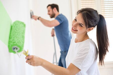 Happy couple painting walls in their new house ready for living together