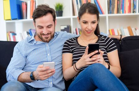 Young couple using smartphone and relaxing at home
