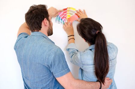 Couple holding paint swatches choosing colors for painting new home Imagens