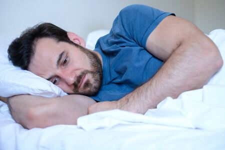 Man feeling negative emotions trying to sleep at night