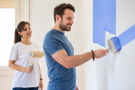 Cheerful smiling couple painting and renovating home together Imagens
