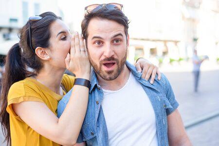 La mujer le susurra te amo al oído de su novio