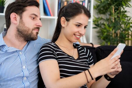 Jealous man spying girlfriend and watching her mobile phone Stockfoto