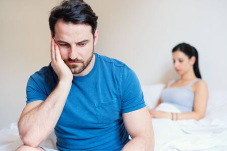 Man sad after arguing with his girlfriend in the bed Stock fotó
