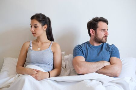 Angry girl and angry man in the morning lying in bed