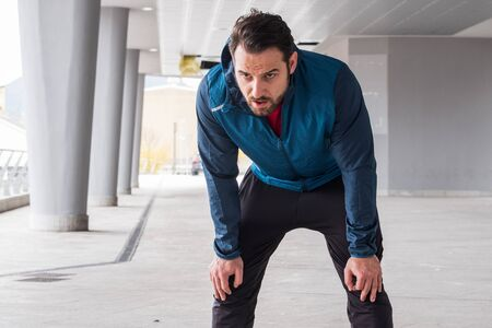 Active man resting during urban running training Imagens