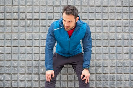 Active man resting during urban running training