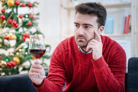Homme triste dans la solitude buvant de l'alcool tout seul pendant Noël
