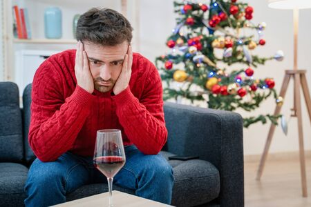Lonely man celebrating christmas and drinking alone