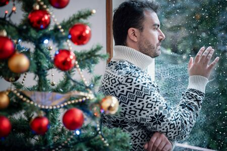 Sad man portrait feeling negative emotions during christmas celebrations
