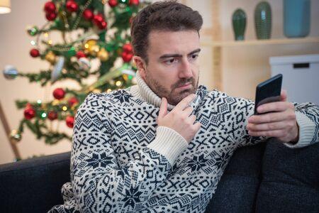 Homme attendant le message de Noël sur le smartphone