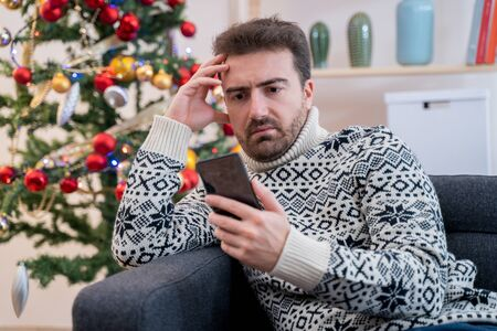 Man waiting for christmas message on smartphone