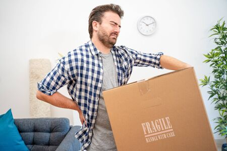 Pain in back. Young man suffering while lifting a cardboard box Stock Photo