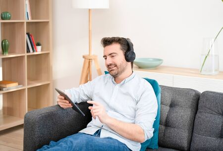 Young man watching streaming movie and using digital tablet lying on sofa relaxation time