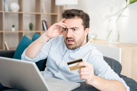 Man at home sitting on sofa with credit card accounting costs, charges, taxes and mortgage for paying bills