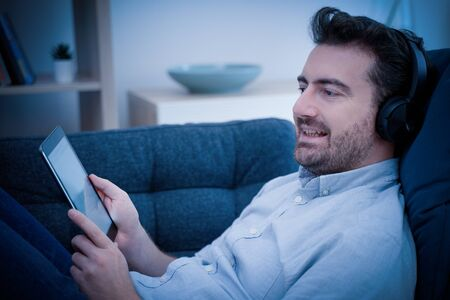Young man watching streaming movie and using digital tablet at night