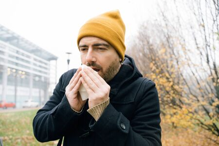Man blowing nose and suffering in cold weather