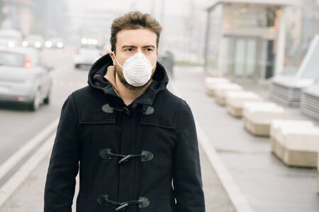 Man walking in city wearing mask against smog air pollution
