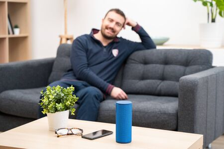 Man using virtual assistant and smart speaker at home Stock Photo