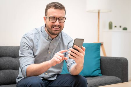Man using virtual assistant and smart speaker at home