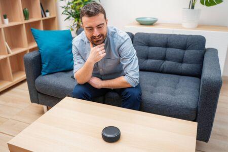 Hombre con asistente virtual y altavoz inteligente en casa Foto de archivo