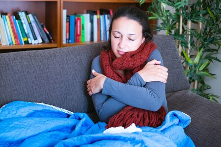 Sick woman covered by a blanket on the sofa with high fever and flu Banque d'images - 138295572