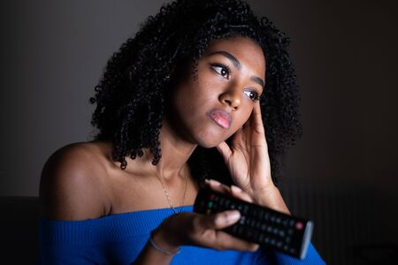 Bored young black woman watching television