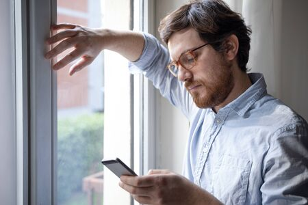 Guy holding cellphone at home next to the window
