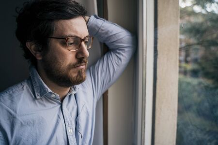 Thoughtful anxious guy looking out the window Stock Photo - 138822945